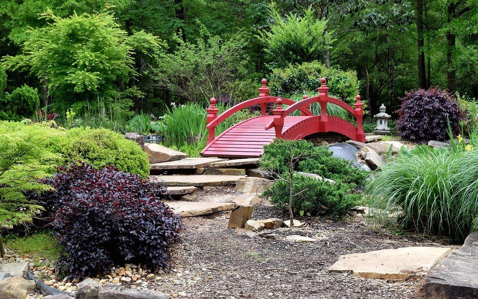 red bridge, stones, and grass for local landscape features